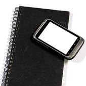 Smartphone på anteckningsbok — Stockfoto