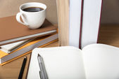 Open notebook with book and coffee cup — Stock Photo