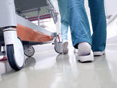 Medical staff moving patient through hospital corridor — Stock Photo