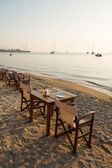 Waterfront cafe table on sandy beach — Stock Photo