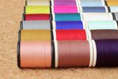 Spools of thread  multicolored on cork board — Stockfoto