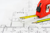 Tape measure and pencil over a construction plan drawing — Stock Photo