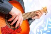 Hand to pluck the strings of a guitar — Stock Photo