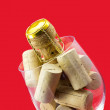 Glass of wine with cork stoppers on red background — Stock Photo #67642955
