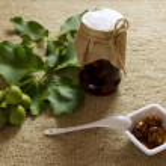Jam jar nuts on textured burlap with leaves, fruit, white cerami — Stock Photo #74788645