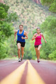 Couple sprinting concentrated on road — Stock Photo