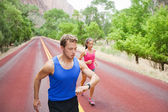 Couple running concentrated on road — Stock Photo