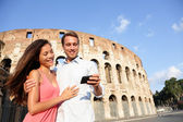 Couple in Rome by Colosseum using smartphone — ストック写真
