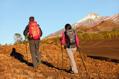 Woman and man walking on hike on volcano Teide — Stock Photo
