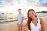 Couple on beach holding hands at sunset — Stock Photo
