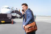Business man on smartphone by plane — Stok fotoğraf