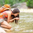 Hiker woman drinking water from river — Stock Photo #54891555