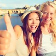 Girlfriends in city giving thumbs up — Stock Photo #54891877