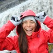 Woman laughing in raincoat near Dettifoss waterfall — Stock Photo #54893257