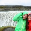 Couple in raincoats near Dettifoss waterfall — Stock Photo #54893263