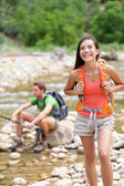 Hikers trekking by river water creek in forest — Stock Photo
