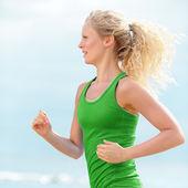 Girl jogging outside on beach — Stock Photo