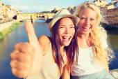 Girlfriends in city giving thumbs up — Stockfoto