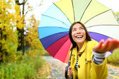 Woman happy in rain with umbrella — Stockfoto