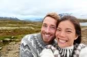 Couple wearing Icelandic sweaters taking selfie — Stock Photo