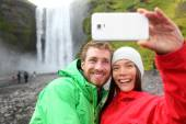 Couple taking picture waterfall  on smartphone — Foto Stock