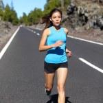 Female runner jogging on road — Stock Photo #55353749