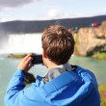 Tourist taking photo of waterfall — Stock Photo #62143271