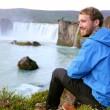 Tourist relaxing by waterfall — Stock Photo #62143479