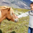 Woman petting Icelandic horses in sweater — Stock Photo #62143763