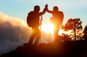 Hiking people reaching summit top high five — Photo