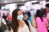 Person wearing protective mask in airport — Stock Photo