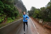 Male runner jogging on road — Stock Photo