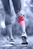 Woman running clutching calf muscle — Stock Photo