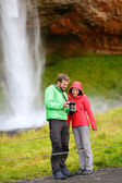Tourists with SLR camera by waterfall — Stock Photo