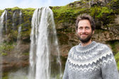Man in Icelandic sweater by waterfall — Stock Photo