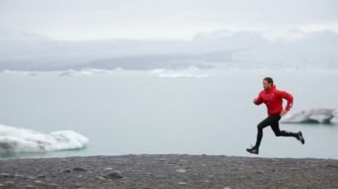 Fit male athlete running by icebergs — Stock Video