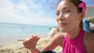 Woman eating sushi take out on beach — Stock Video