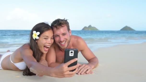Pareja tomando selfie tumbado en la playa — Vídeo de stock