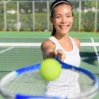 Woman showing tennis ball and racket — Stock Photo #72655137