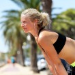 Fit woman taking break while jogging — Stock Photo #72655183