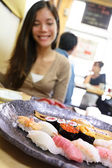 Sushi eating woman in Tokyo restaurant — Stock Photo