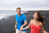 Couple laughing together walking on beach — Stock Photo