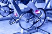 Female athlete's legs using bicycle machine — Stock Photo