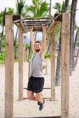 Fitness man on monkey bars — Stock Photo