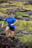 Man trail running on volcanic rocks — Stock Photo