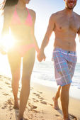 Couple walking in beach sunset — Stock Photo