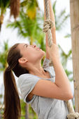 Woman doing body workout on climbing rope — Stock Photo