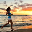 Woman jogging at beach sunrise — Stock Photo #73838629