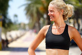 Woman runner listening to music in earbuds — Stock Photo