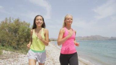 Lopende vrouwen joggen op strand — Stockvideo